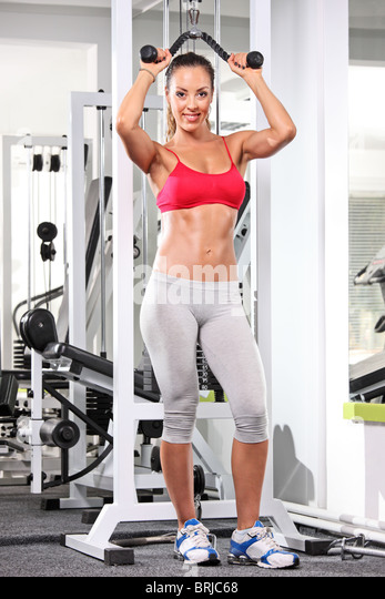 A full length portrait of a woman working out on a fitness equipment - Stock Image