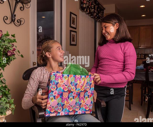 interracial multicultural multi ethnic Korean and Brazilian best girl friends opening birthday presents gifts. MR - Stock-Bilder
