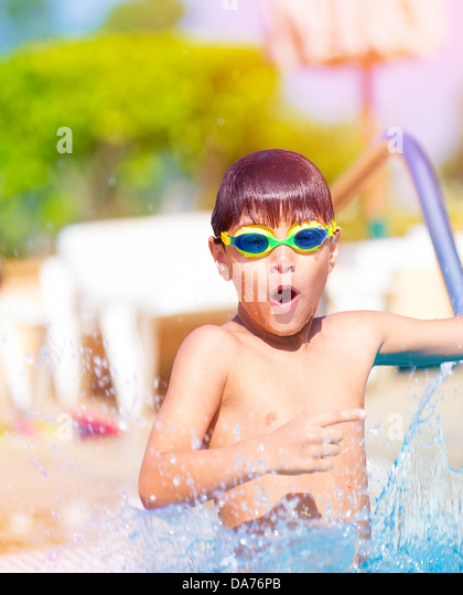 Closeup on pretty boy having fun in the pool, adorable child wearing swimming goggles, summer holidays on luxury - Stock-Bilder