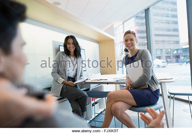 Business people meeting at desk in urban office - Stock Image