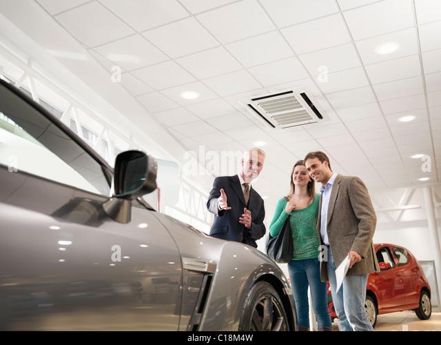 Salesman shows customers car - Stock Image