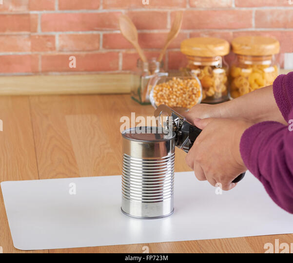 woman opening a can of corn with can opener in the kitchen - Stock Image