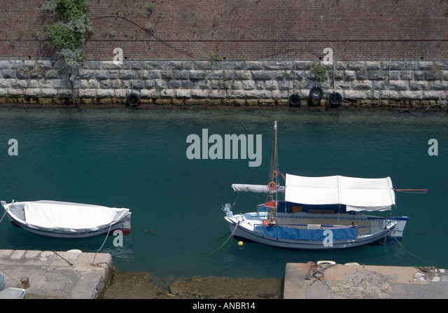 Boats, Contras Fossa moat, Corfu town,  Kerkyra, Greece, boat wooden typical moored mooring pontoon Contras Fossa - Stock Image