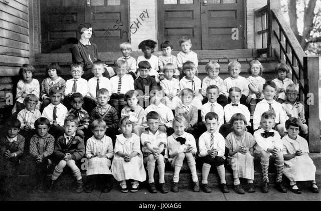 Class portrait of 38 young students with female teacher, all white except for one African American girl, wearing - Stock Image