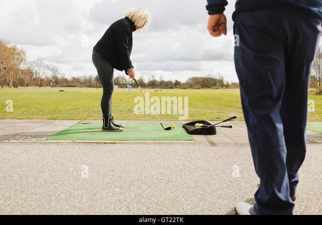 Friends practicing golf at driving range - Stock-Bilder