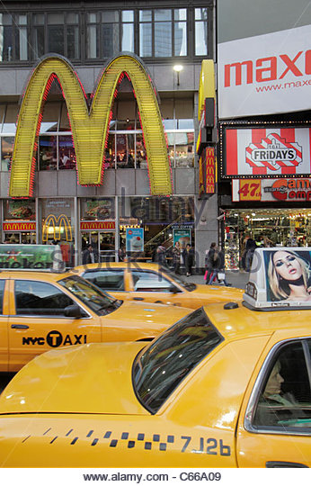 New York New York City NYC Manhattan Midtown Times Square taxi cab yellow McDonald's fast food restaurant golden - Stock Image