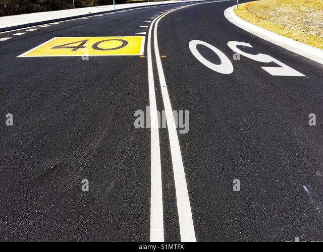 Bend in road with double lines, large 50 and 60 speed limit painted on asphalt. Australia - Stock Image