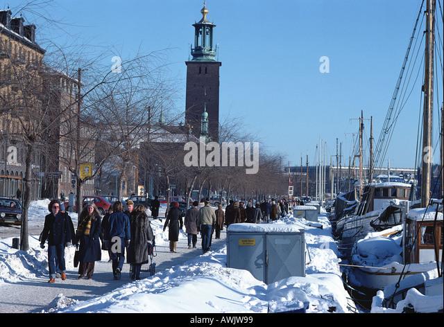 Sweden, Stockholm, people walking alongside quay with docked boats - Stock Image