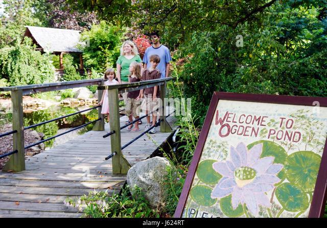 Indiana Valparaiso Ogden Gardens botanical horticulture native plants pond wood bridge man woman boy girl parent - Stock Image