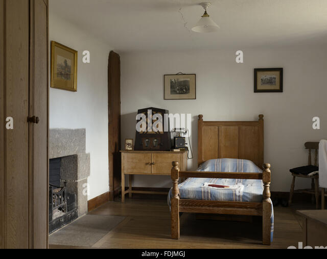 The Manservant's Room with a wooden bed and bedside cupboard, and a radio at Castle Drogo, Devon. - Stock-Bilder