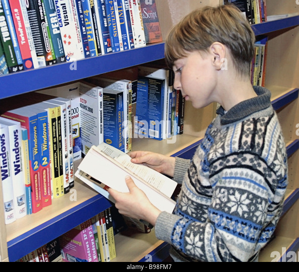 Boy chooses book at a store of Prosveshcheniye Education publishing house offering textbooks teaching aids maps - Stock Image