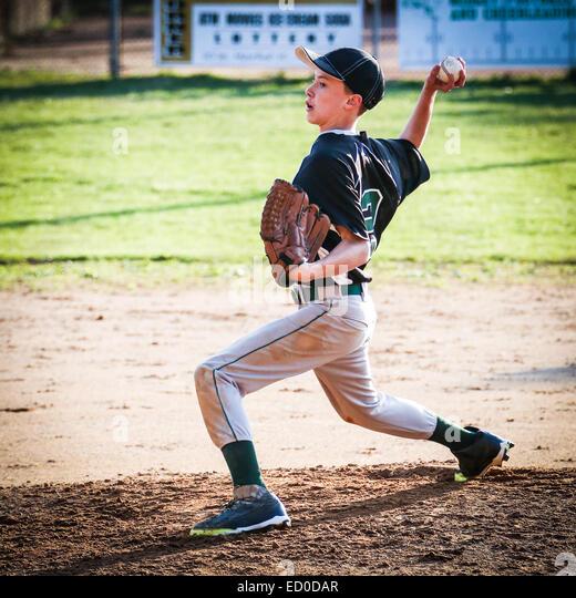 USA, Young boy (10-11) pitching on pitchers mound - Stock Image