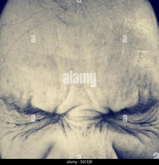 Man with eyes tightly shut close up. - Stock Image