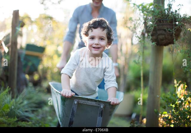 Portrait of boy riding in wheelbarrow on allotment - Stock-Bilder