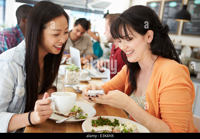Two Female Friends Friends Meeting For Lunch In Coffee Shop - Stock Image