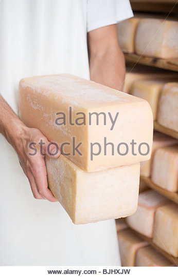 Man holding two blocks of cheese in a cheese dairy - Stock Image