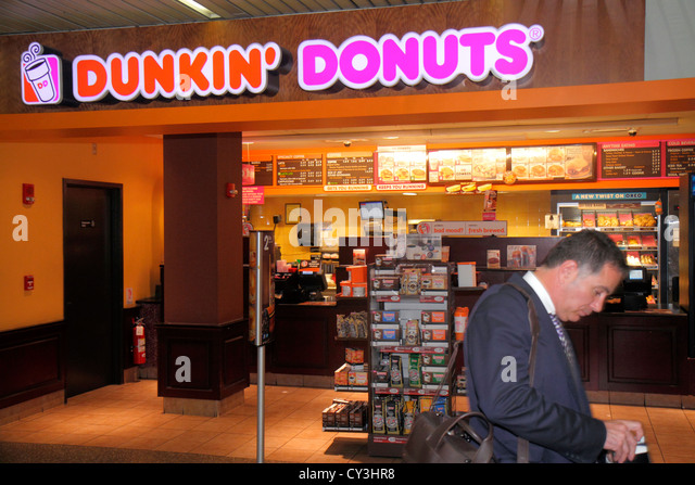 Massachusetts Boston Logan International Airport BOS concourse terminal Dunkin' Donuts coffee food snacks doughnuts - Stock Image