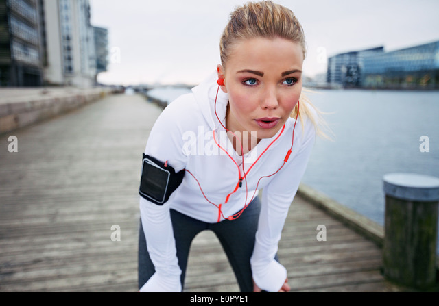 Young woman taking a break from exercise outdoors. Fit young female athlete stopping for rest while jogging along - Stock Image