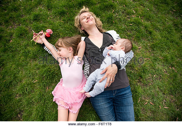 Mother and children laying in grass - Stock-Bilder