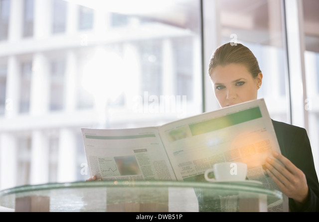 Businesswoman reading newspaper at office cafe - Stock-Bilder