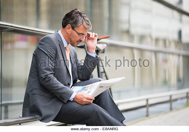 Mature businessman sitting outside office reading newspaper - Stock Image