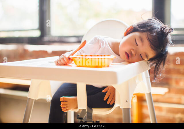 One year old baby girl asleep in highchair at breakfast - Stock Image