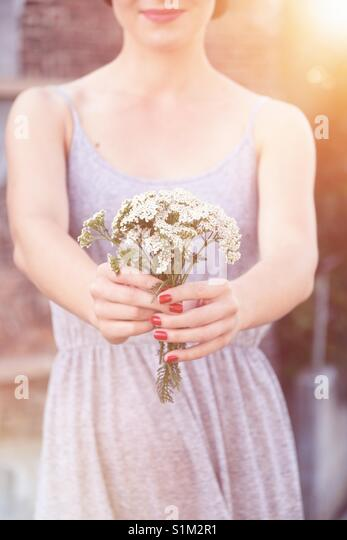 Young woman holding fresh flowers - Stock Image