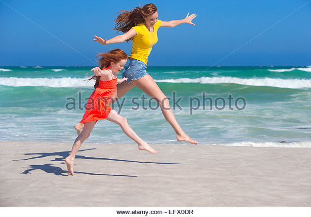 Mother and daughter leaping, with arms outstretched, on sunny beach - Stock Image