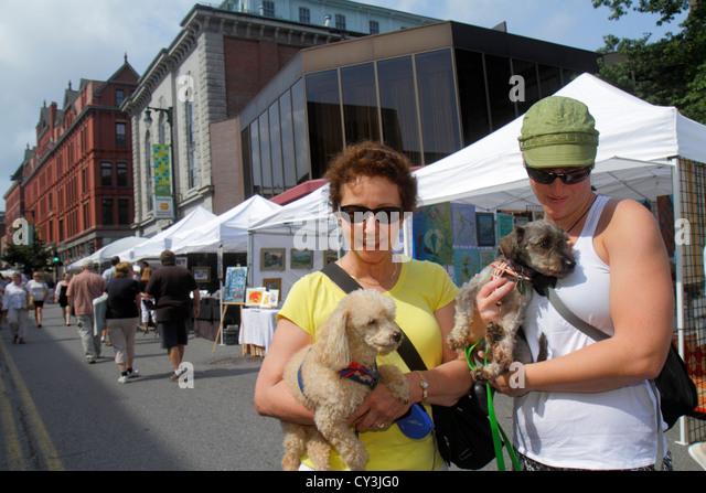 Portland Maine Congress Street WCSH 6 Sidewalk Art Festival artists vendors shopping historic buildings woman dog - Stock Image