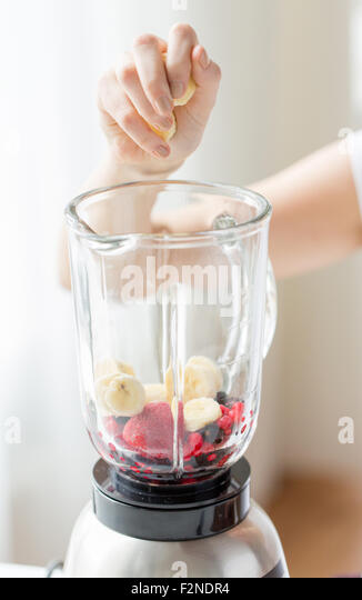 close up of woman hand adding fruits to blender - Stock-Bilder