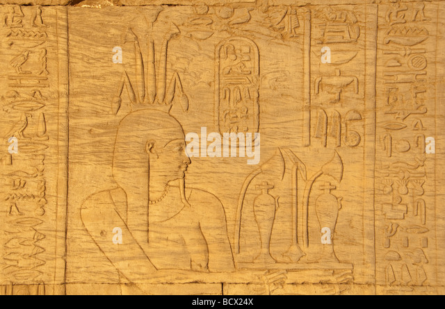 Egypt Kom Ombo temple hieroglyph carving relief pharaoh wearing crown lotus flowers - Stock Image