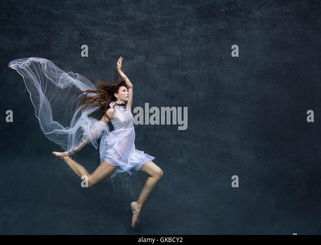 Young brunette dancer in pool in a white dress, Virginia Beach, VA - Stock Image