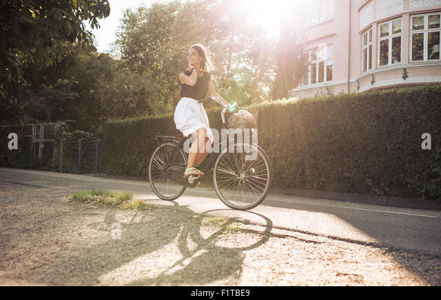 Pretty young woman enjoying bicycle ride through the street. Female looking away smiling while cycling. - Stock Image