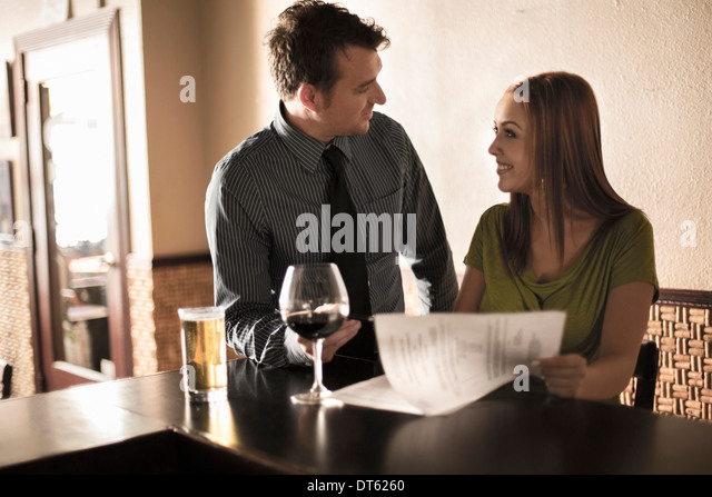 Businessman and woman looking at contract in a wine bar - Stock-Bilder