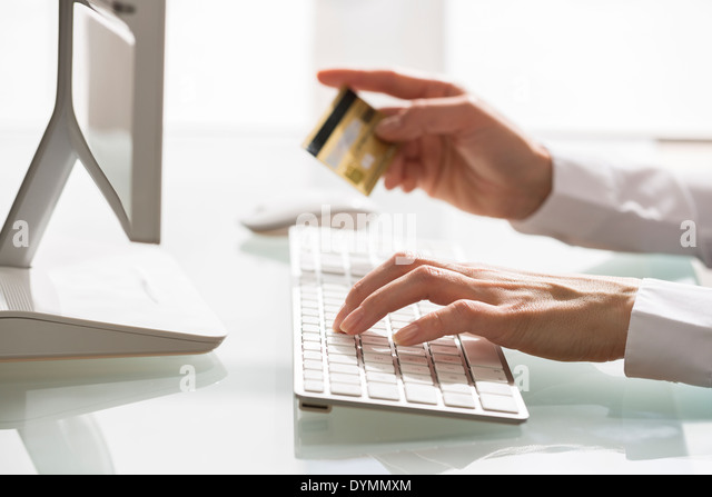 Woman Shopping on internet using computer and credit card - Stock Image