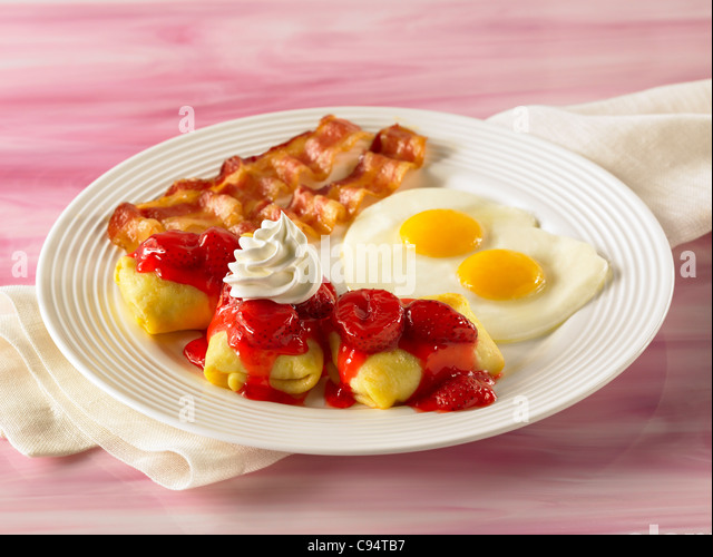 Breakfast cheese crepe blintz with fruit sauce topped with whip cream with two eggs and bacon - Stock Image