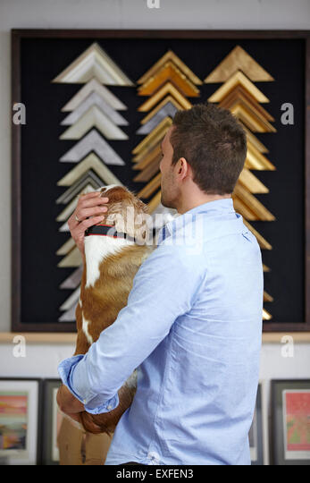 Man carrying dog whilst choosing frame in picture framers workshop - Stock Image