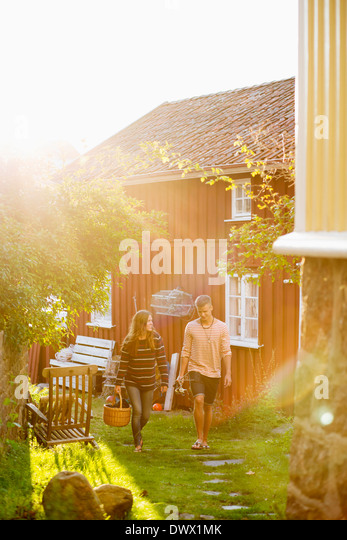 Full length couple walking together in yard - Stock Image