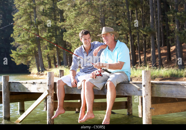 Father and adult son fishing , - Stock Image
