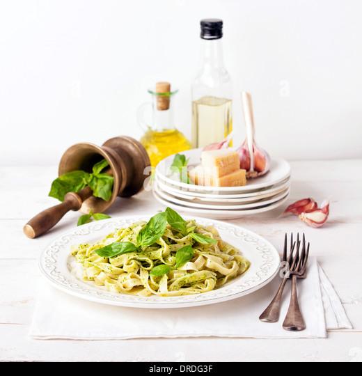 Pasta with pesto on white plate - Stock Image