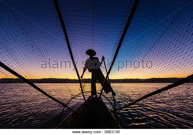 Silhouette of fisherman rowing canoe on water - Stock Image