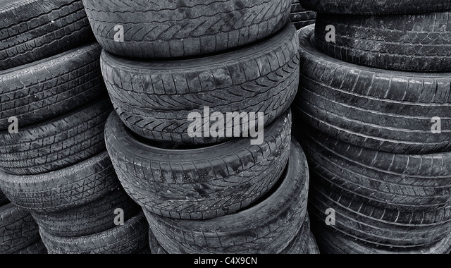 Stacks of old used recycled tires. - Stock Image