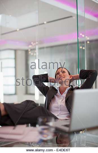 Businesswoman sitting at desk with laptop - Stock Image