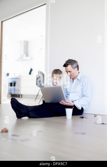Man sitting on floor using laptop, son watching - Stock-Bilder