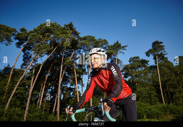 Mature cyclist riding past forest - Stock-Bilder