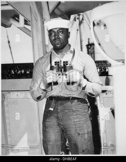 Looking to sea from the signal bridge is Napoleon Reid, Seaman 2-c., USNR, shown standing on lookout watch on a - Stock-Bilder