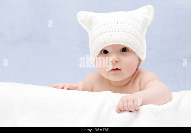 Beautiful baby in white hat lies on bed - Stock Image