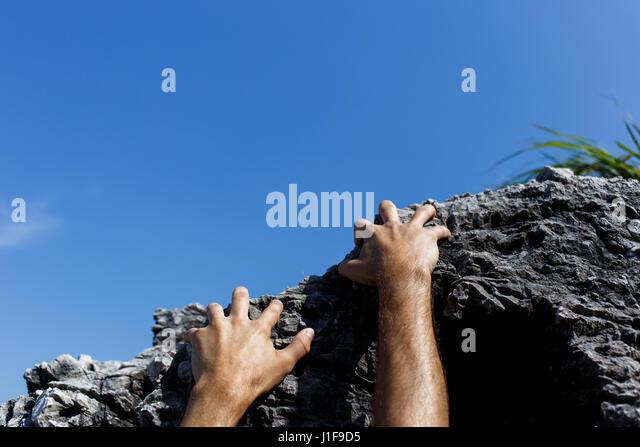 Man climbs on mountain slope - Stock Image