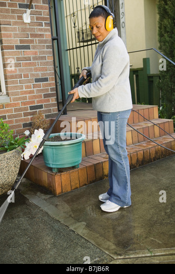 African American woman using a power washer, Vancouver, BC - Stock Image