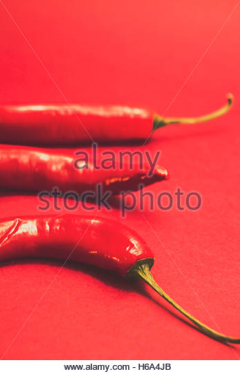Retro toned food photo on hot mexican chili peppers on pink background. Spice of still life - Stock Image